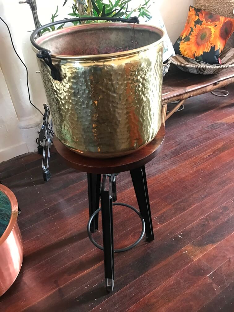 A brass pot which has been restored by polishing and powder coating the handle black
